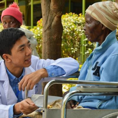An intern working with a patient on our medical internship for teenagers in Kenya